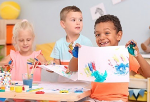 a boy shows off his finger painting at a 24-hour daycare
